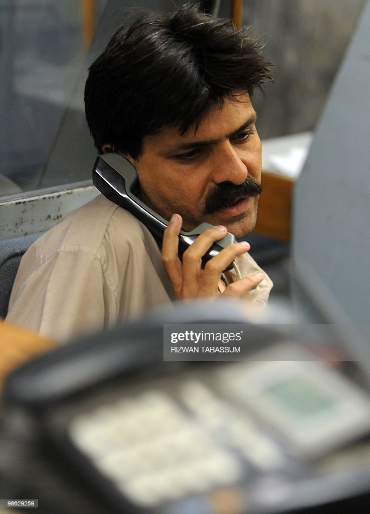 A Pakistani stockbroker talks to a client as he trades at a trading session at the Karachi Stock Exchange (KSE) on April 23, 2010. The benchmark KSE-100 index was 10593.03, down 22.12 points in the morning session.