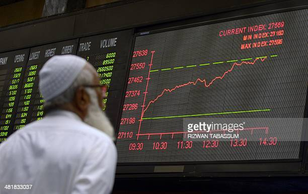 A Pakistani stockbroker watches latest share prices on a digital board during a trading session at the Karachi Stock Exchange in Karachi on April 1...