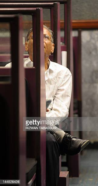 A Pakistani stockbroker watches the latest share prices on a monitor during a trading session at The Karachi Stock Exchange in Karachi on May 15 2010...