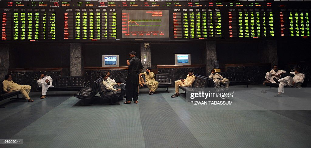 Pakistani stockbrokers discuss under a latest share prices digital board during a trading session at the Karachi Stock Exchange (KSE) on April 23, 2010. The benchmark KSE-100 index was 10593.03, down 22.12 points in the morning session.