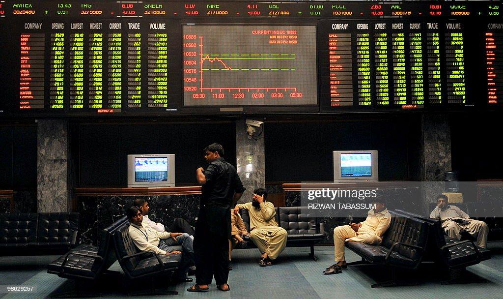 Pakistani stockbrokers discuss under a l : Nieuwsfoto's