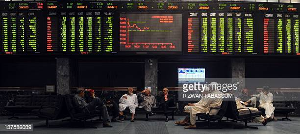 Pakistani stockbrokers gather under an index board during a trading session at the Karachi Stock Exchange in Karachi on January 23 2012The benchmark...