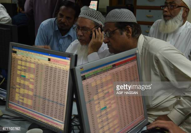 Pakistani stockbrokers look on during a trading session at the Pakistan Stock Exchange in Karachi on April 21 2017 The benchmark PSE100Index was...
