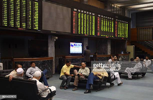 Pakistani stockbrokers monitor and discuss as they sit under an index board during a trading session at the Pakistan Stock Exchange in Karachi on...