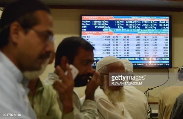 Pakistani stockbrokers monitor share prices at the Pakistan Stock Exchange in Karachi on October 9, 2018. - The International Monetary Fund said...