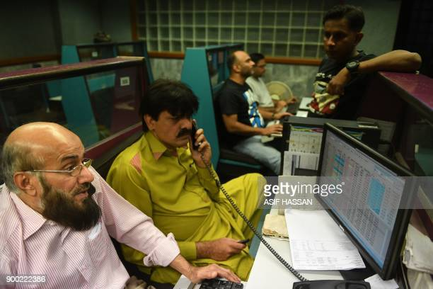 Pakistani stockbrokers monitor shares during a trading session at the Pakistan Stock Exchange in Karachi on January 1 2018 / AFP PHOTO / ASIF HASSAN