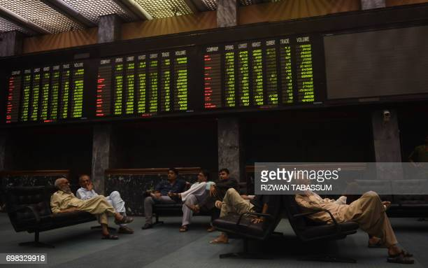 Pakistani stockbrokers sit under an index board showing the latest share prices during a trading session at the Pakistan Stock Exchange in Karachi on...
