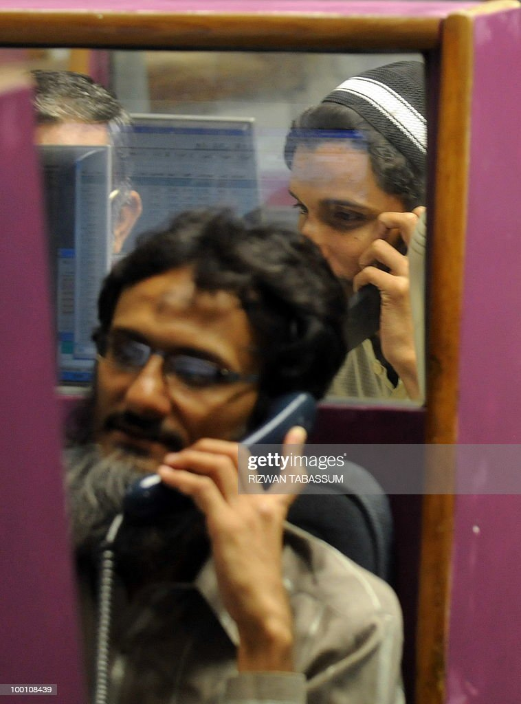 Pakistani stockbrokers talk on phones as they watch the latest share prices during a trading session at the Karachi Stock Exchange (KSE) on May 21, 2010. The benchmark Karachi Stock Exchange (KSE) 100-index was 9881.65, down 111.75 points. AFP PHOTO/Rizwan TABASSUM