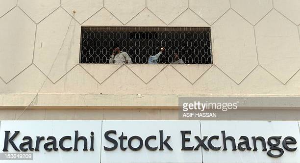 Pakistani stockbrokers talk on their mobile phones at the Karachi Stock Exchange building during a trading session on May 17 2010 The benchmark KSE...