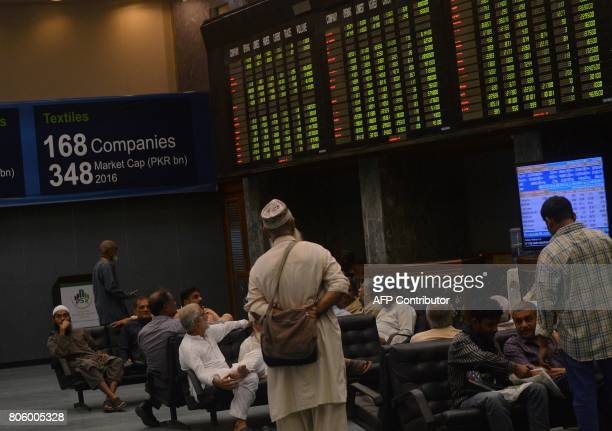 Pakistani stockbrokers watch an index board displaying the latest share prices during a trading session at the Pakistan Stock Exchange in Karachi on...