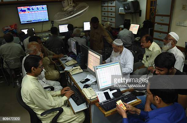 Pakistani stockbrokers watch share prices on computer monitors during a trading session at the Pakistan Stock Exchange in Karachi on September 21...