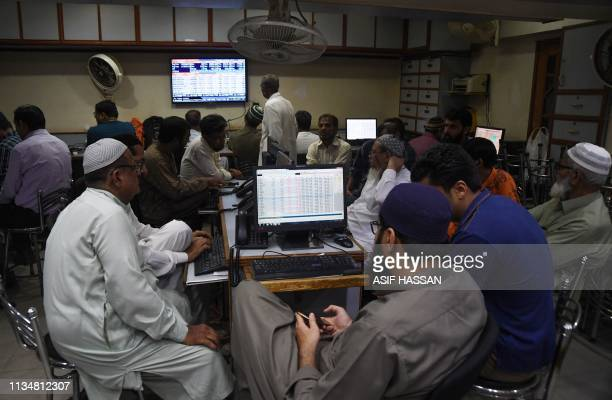 Pakistani stockbrokers watch the latest share prices during a trading session at the Pakistan Stock Exchange in Karachi on April 4 2019