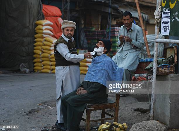 A Pakistani street barber gives a customer a shave at a market in Rawalpindi on January 24 2014 In the last fiscal year Pakistan's economy grew at 36...