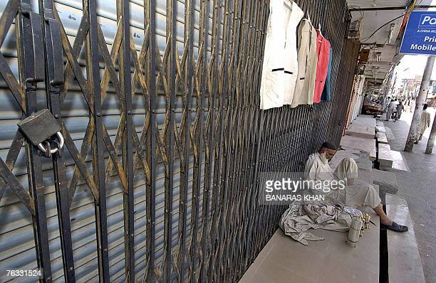 A Pakistani street vendor sits in front of shuttered market during a strike in Quetta 26 August 2007 on the first death anniversary of...