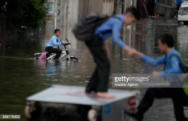Pakistani student helps his colleauge to reach on a waste caontainer lying on a flooded street after heavy monsoon rains hit the city of Rawalpindi...