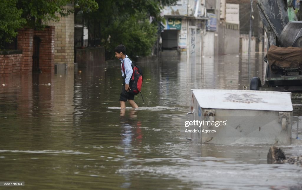 Pakistani student wades through a flooded street after heavy monsoon rains hit the city of Rawalpindi Pakistan on August 25 2017 Heavy monsoon rains..