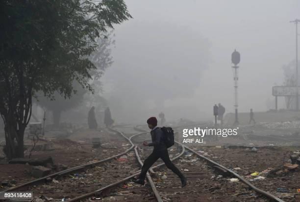 A Pakistani student walks through dense fog across railway tracks on the outskirts of Lahore on December 15 2017 / AFP PHOTO / ARIF ALI