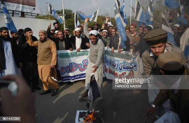 Pakistani students burn images of US President Donald Trump during a protest against aid cuts in Islamabad on January 5 2018 The United States added...