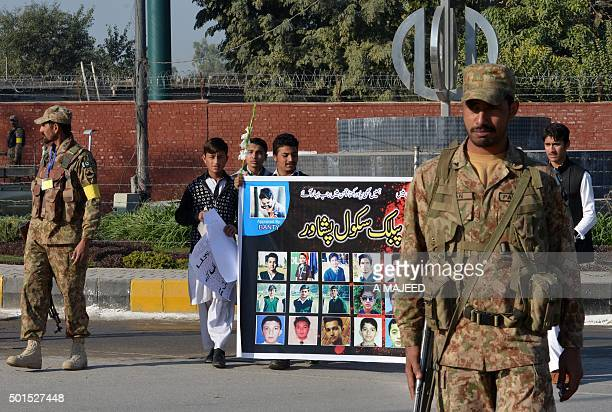 Pakistani students carry a banner bearing images of victims of the Peshawar school massacre as army troops cordon off a street leading to the Army...