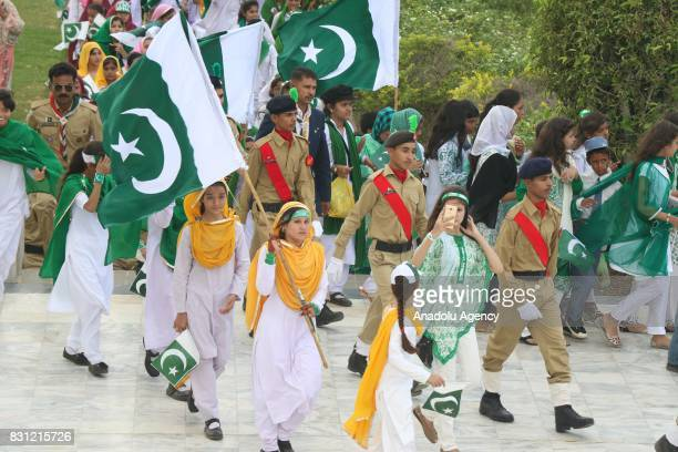 Pakistani students carry national flag at the mausoleum of the founder of Pakistan Muhammad Ali Jinnah during a ceremony to mark the countrys...