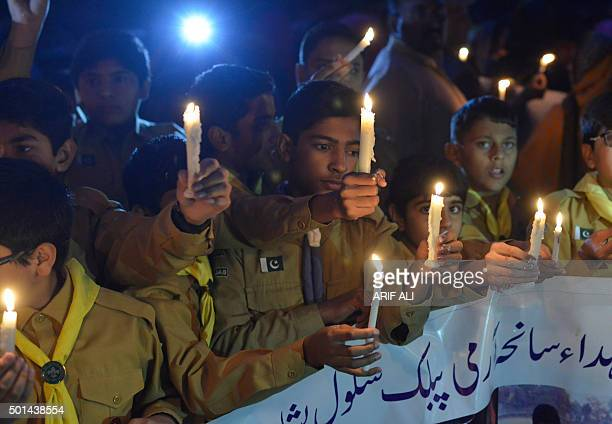 Pakistani students hold burning candels during a vigil to pay tribute to the victims of the Peshawar school massacre of December 16 the deadliest...