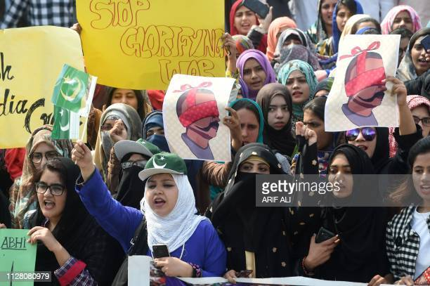 Pakistani students hold placards with the image of Abhinandan Varthaman the Indian Air Force pilot captured by Pakistan authorities in...