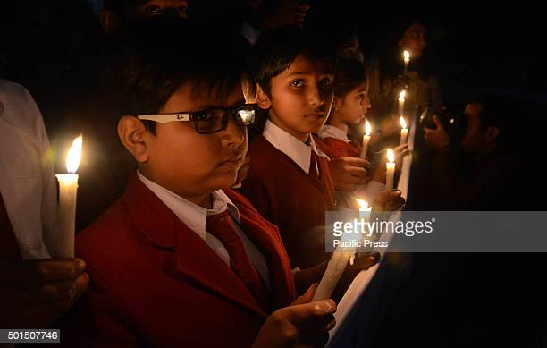 Pakistani students lit candles during a vigil to pay tribute to the victims of the Peshawar school massacre of December 16 the deadliest terror...
