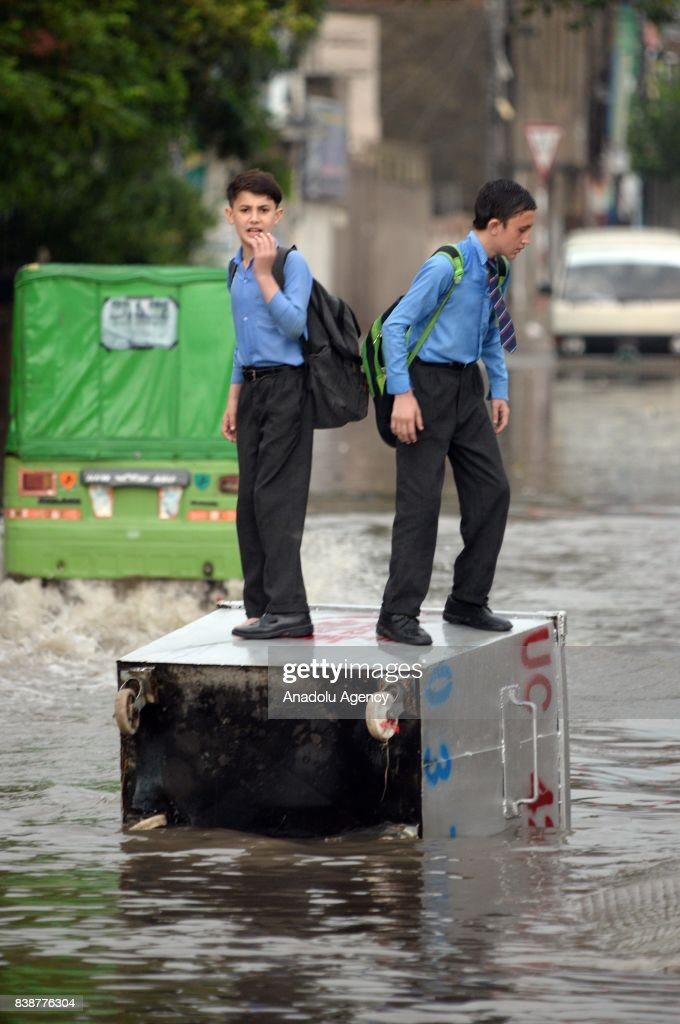 Pakistani students stand on a waste caontainer lying on a flooded street after heavy monsoon rains hit the city of Rawalpindi Pakistan on August 25...