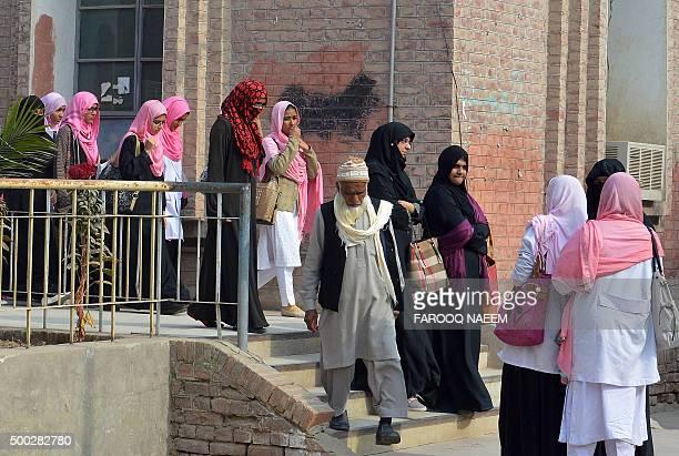 Pakistani students walk outside the pharmacy department at Bahauddin Zakariya University in Multan on December 7 where female US shooter Tashfeen...