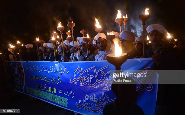 Pakistani studentsteachers and civil society activists hold burning torches during a vigil to pay tribute to the victims of the Peshawar school...