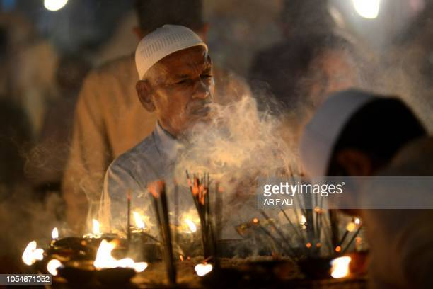 Pakistani Sufi disciples light candles and incense at the Data Darbar complex during the threeday annual 'Urs' religious festival in Lahore on...