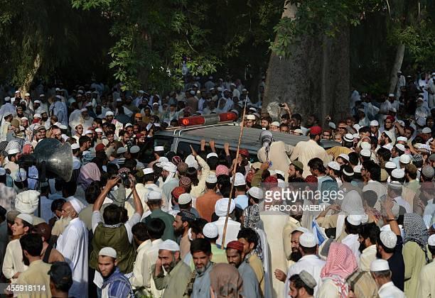 Pakistani Sunni Muslims surround the ambulance carrying the coffin of Mufti Amanullah from the hardline Sunni organisation Ahle Sunnat Wal Jamaat...