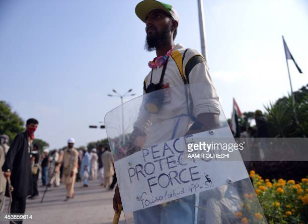 A Pakistani supporter of Canadabased preacher TahirulQadri looks on during a protest near government ministry buildings in Islamabad on August 20...