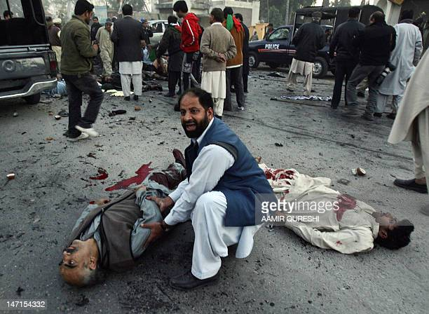 A Pakistani supporter of former premier Benazir Bhutto shouts for help as he sits next to an injured at the suicide attack site in Rawalpindi 27...