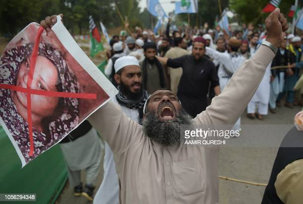 Pakistani supporter of the Ahle Sunnat Wal Jamaat a hardline religious party holds an image of Christian woman Asia Bibi during a protest rally...