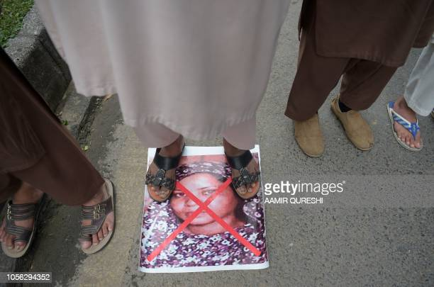 Pakistani supporter of the Ahle Sunnat Wal Jamaat a hardline religious party stands over an image of Christian woman Asia Bibi as they march during a...