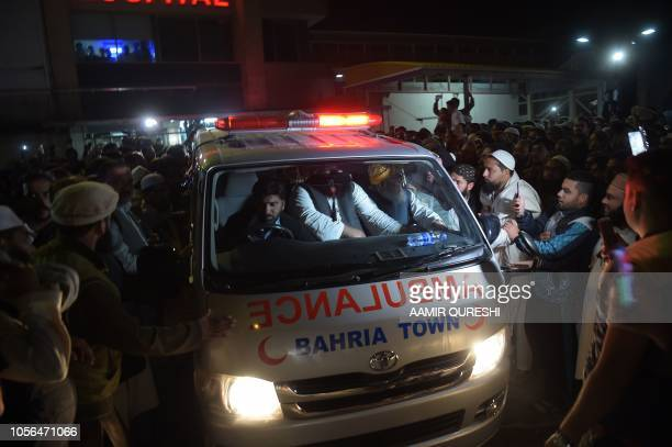 Pakistani supporters gather around an ambulance carrying the body of a key cleric Maulana Sami ulHaq who was killed during an attack outside a...