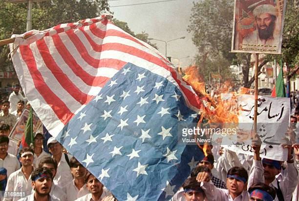 Pakistani supporters of Afghanistan's ruling Taliban Islamic militia burn an American flag at a protest rally October 18 2001 in Lahore Pakistan The...