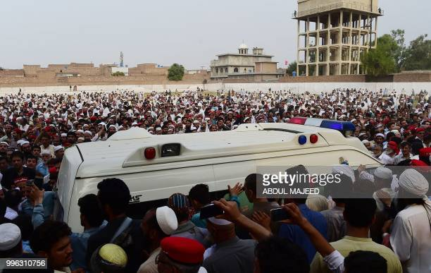 Pakistani supporters of Awami National Party gather around an ambulance carrying the body of a local leader and candidate of ANP Haroon Bilour during...
