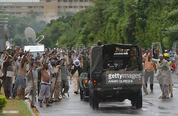 Pakistani supporters of Canadian cleric Tahir ul Qadri and cricketturned politician Imran Khan carrying sticks cheer as security personnel pass near...