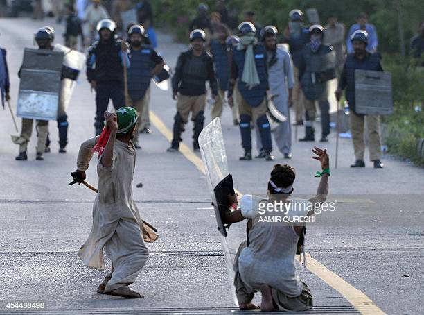 Pakistani supporters of Canadian cleric Tahir ul Qadri and cricketturned politician Imran Khan face riot police during an antigovernment protest in...