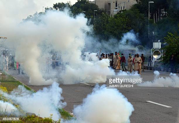 Pakistani supporters of cricketerturned politician Imran Khan and Canadian cleric Tahir ul Qadri clash with riot police amidst teargas during an...