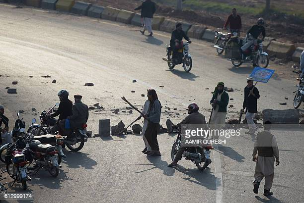 Pakistani supporters of former police bodyguard Mumtaz Qadri carry sticks as they stop motorcyclists and block a highway during a protest against...