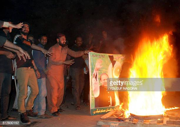 Pakistani supporters of former police bodyguard Mumtaz Qadri torch a banner bearing an image of Prime Minister Nawaz Sharif during a protest against...