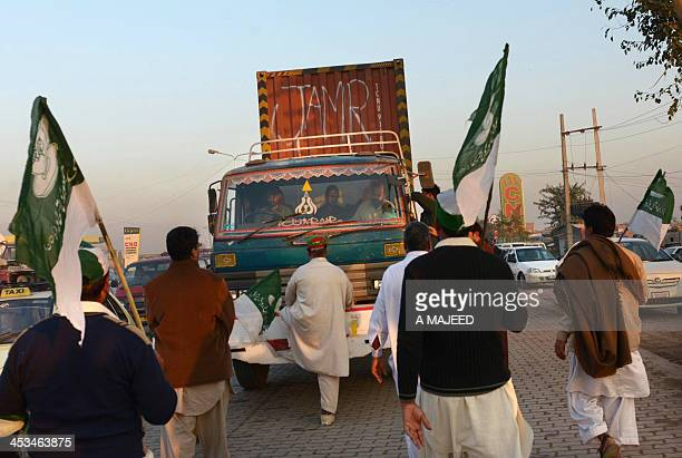 Pakistani supporters of Imran Khan head of Pakistan TehreekeInsaf party stop a truck to check the documents at an unofficial checkpoint in a bid to...