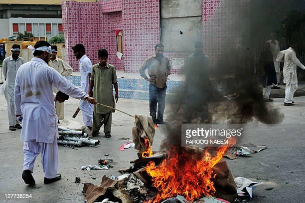 Pakistani supporters of Malik Mumtaz Hussain Qadri burn material, after the court announced the death sentence for Qadri in Rawalpindi on October 1,...