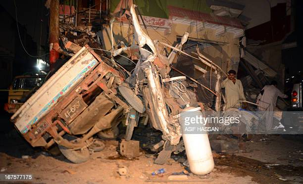 Pakistani supporters of Pashtundominated Awami National Party look at the wreckage of a vehicle and destroyed office following a bomb explosion in...
