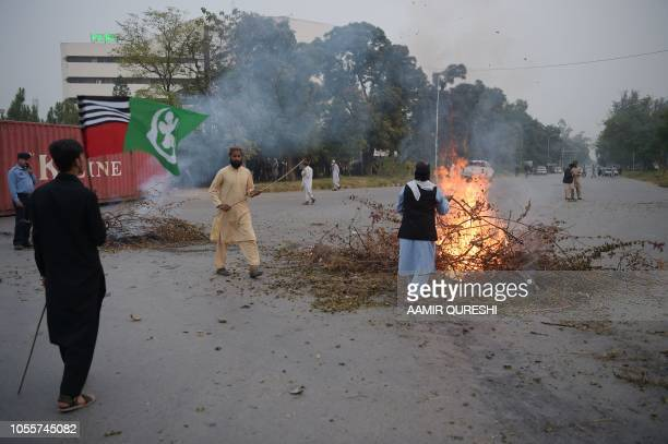 Pakistani supporters of the Ahle Sunnat Wal Jamaat a hardline religious party burn tree branches to block a street leading to Pakistan's Supreme...