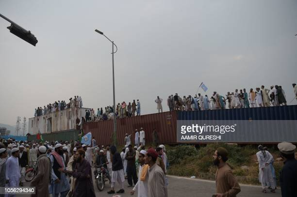 Pakistani supporters of the Ahle Sunnat Wal Jamaat a hardline religious party gather on containers set up to block a street during a protest rally...