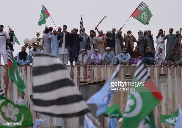 Pakistani supporters of the Ahle Sunnat Wal Jamaat a hardline religious party stand on a container set up to block a street during a protest rally...